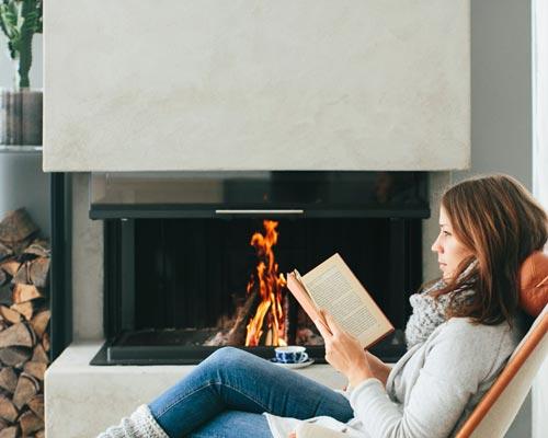 خانمی در حال مطالعه در کنار شومینه که با چوب تولید گرما می کند