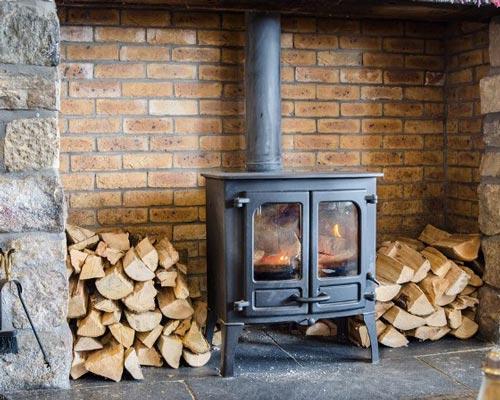 شومینه چوبی با قطعات چوب در کنار آن نشان داده شده اند