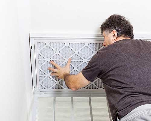 یک مرد در حال تعویض فیلتر دستگاه تصفیه هوا