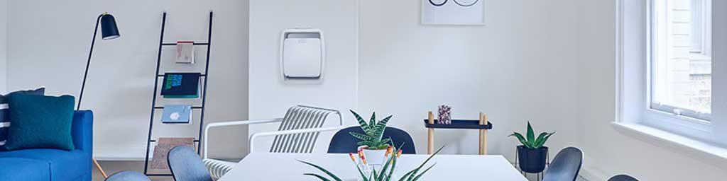 دستگاه تصفیه هوا در یک خانه آویزان روی دیوار و یک گلدان روی میز
