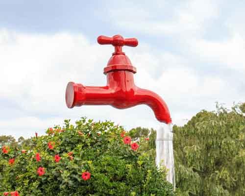 يک شير آب قرمز رنگ که به شکل معلق در هوا قرار دارد و از شير آن آب به سمت پايين در حال ريزش است