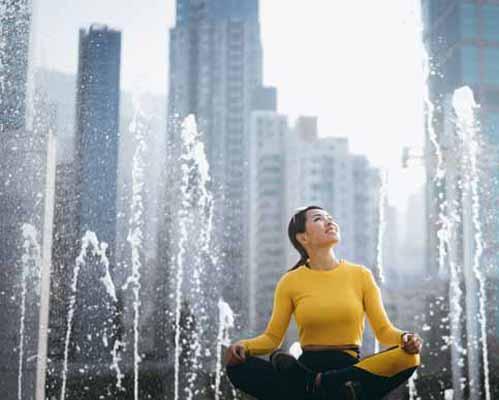 آبشار موزيکال که در وسط شهر نصب شده است و خانمي که جلوي آبشار نشسته است