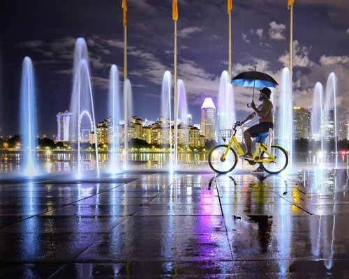 آبنماي کف خشک که در شهر قرار گرفته و فردي با دوچرخه در حال عبور از آنجا است