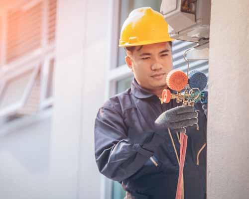 مردي که در حال انجام دادن برق کشي است و روبه روي ديوار ايستاده است