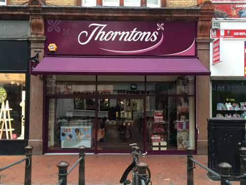 يک مغازه که ورودي آن آفتابگير نصب شده است و اجناس از پشت شيشه مغازه به چشم مي خورند