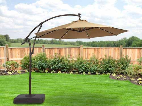 سايبان چتري که در محيط سر سبز نصب شده است و اطراف آن را گياهان متنوع و ديوار احاطه کرده است